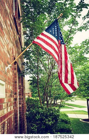 Patriotic American flag hanging in front of a home