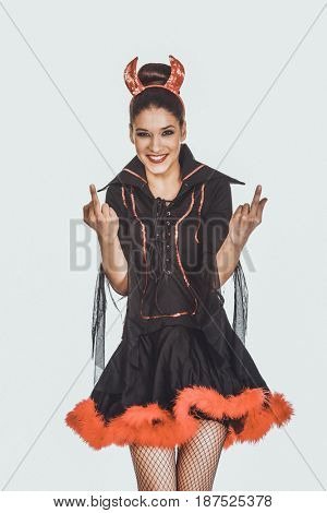 Woman in devil costume with thumbs up.
