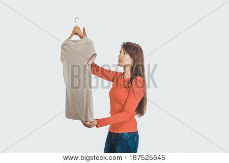 Happy woman looking at new shirt.