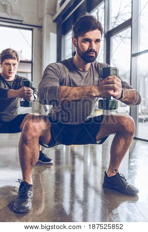 Muscular young men in sportswear with dumbbells exercising at the gym
