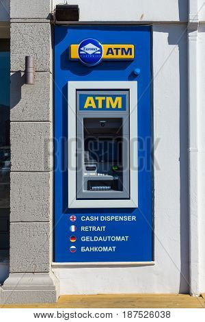 CRETE GREECE - JULY 11 2016: ATM Euronet in the coastal town of Agios Nikolaos. Euronet Worldwide is a US provider of electronic payment services and offers ATM credit and debit card services and other electronic financial services.