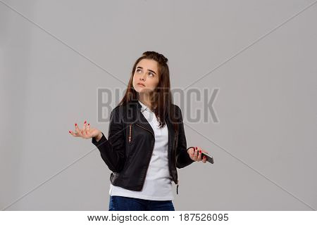 Young beautiful girl holding phone, thinking, gesturing over purple background. Copy space.