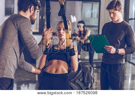 Sportive Woman Exercising With Trx Gym Equipment With Trainers Near By