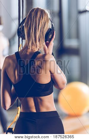 Back View Of Woman Listening Music In Headphones Near Trx Equipment In Gym