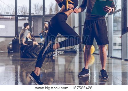 partial view of man helping sportive woman exercising with trx gym equipment