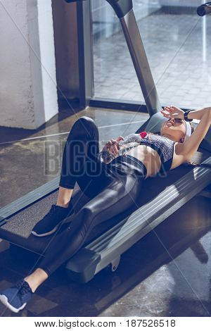 side view of tired sportive woman lying on treadmill in gym
