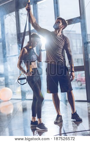 side view of man helping sportive woman exercising with trx gym equipment
