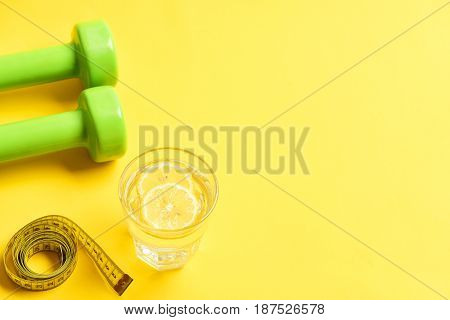 Diet Concept With Dumbbells, Measuring Tape And Water With Lemon