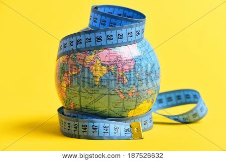 Measuring tape wrapped around terrestrial globe isolated on yellow background. Symbol of worldwide economy population and migration issues