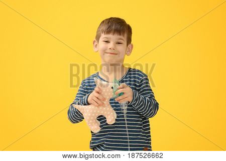 Cute little boy holding nebulizer and toy on color background. Allergy concept