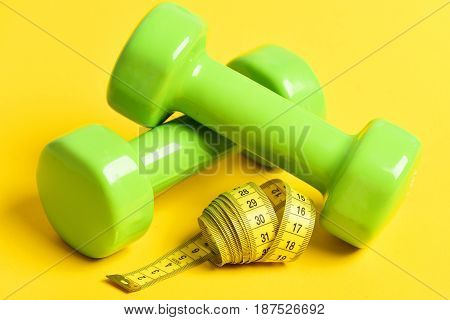 Exercise Concept With Dumbbells And Measuring Tape