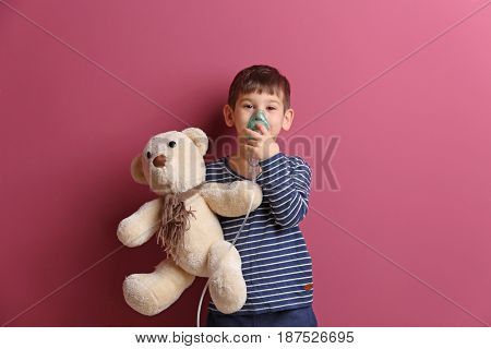 Cute little boy using nebulizer on color background. Allergy concept