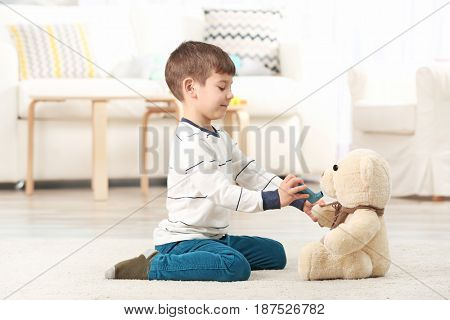 Cute little boy playing with inhaler at home. Allergy concept