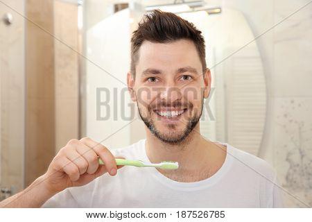Handsome young man brushing teeth in bathroom