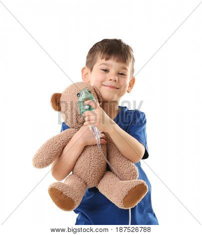 Cute little boy holding nebulizer and toy bear on white background. Allergy concept