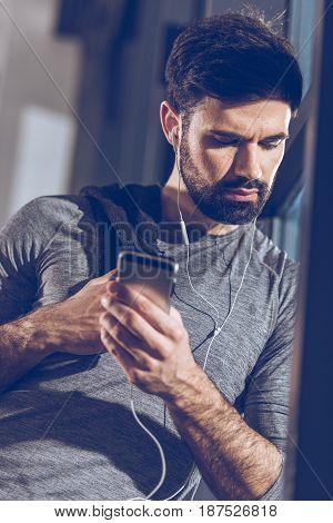Portrait Of Man Listening Music In Earphones After Training