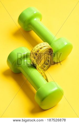 Dumbbells In Green Color With Tape-measure On Yellow