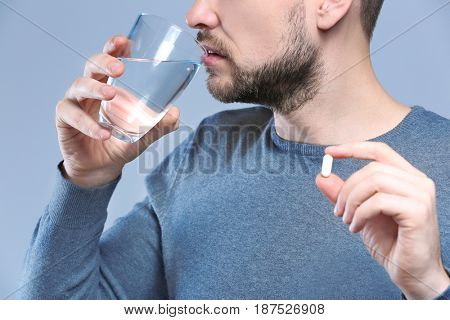 Handsome young man taking pill on color background, closeup
