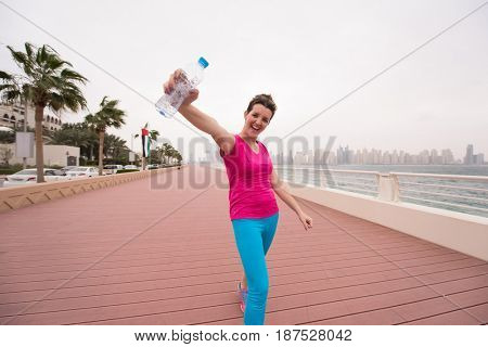 young woman celebrating a successful training run on the promenade by the sea with a bottle of water and her hands raised in the air with a big city in the background