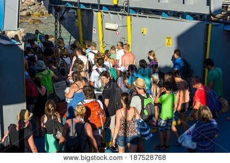 CRETE GREECE - JULY 14 2016: Ferry at the pier. Out of passengers from the ferry. The small village of Chora Sfakion Chania region of Crete.