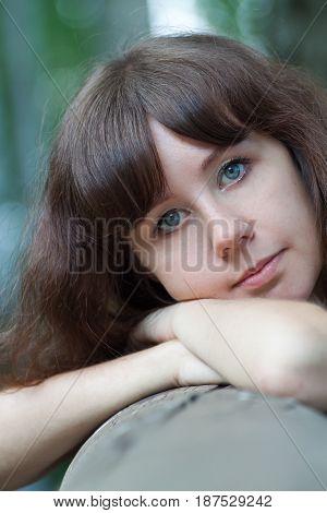 Lovely pensive girl looks straight, portrait close-up