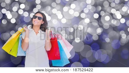 Digital composite of Happy woman carrying shopping bags over bokeh