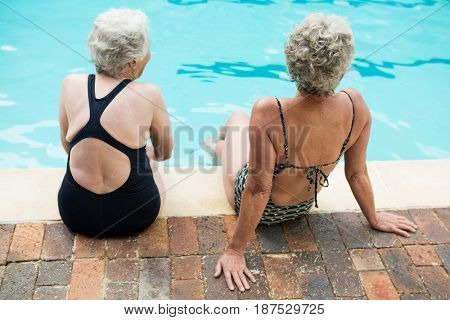 Rear view of two senior women sitting together at poolside
