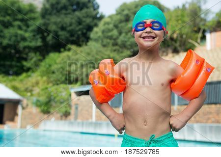 Portrait of boy wearing arm band standing at poolside
