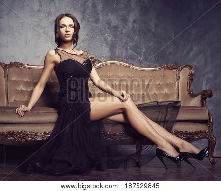 Beautiful and young woman posing in black dress on brown sofa. Vintage interior and retro background.