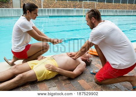 Lifeguards pressing chest of unconscious senior man at poolside
