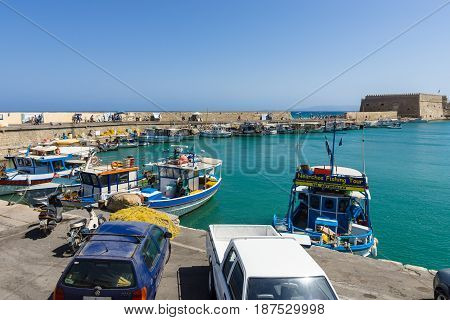HERAKLION GREECE - JULY 16 2016: Crete. Moored fishing boats in the seaport. In the background an old Venetian fortress.