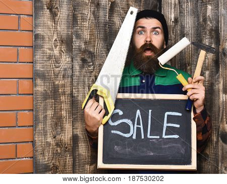 bearded man long beard brutal caucasian hipster with moustache holding various building tools: saw hammer roller paint and board with inscription sale surprised face on brown wooden background