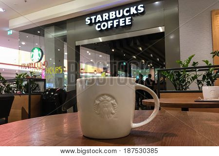 Krakow Poland - May 21 2017: Starbucks coffee sign and coffee tables in front of the coffeehouse entrance. Starbucks Corporation is an American famous coffee company and coffeehouse chain