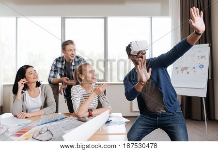 Progressive development. Handsome good looking emotional man standing in the office and being in the virtual reality while wearing VR glasses