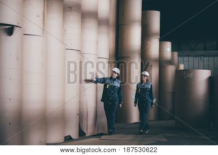 worker walking through storage with paper rolls