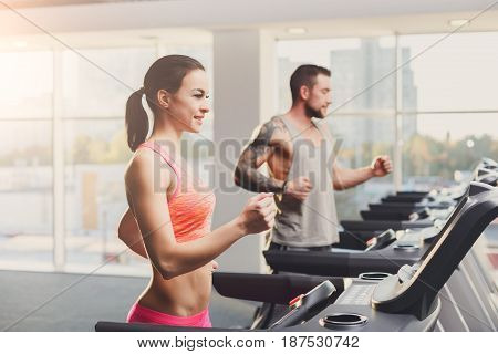 Couple run on treadmills. Man and woman cardio workout in fitness club. Healthy lifestyle, training in gym. Flare effect