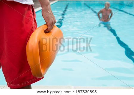 Mid section of lifeguard holding rescue buoy at poolside