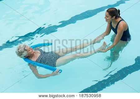 Elevated view of smiling female coach helping senior woman in swimming pool