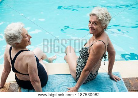 Smiling two senior women sitting together at poolside