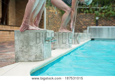 Low section of two senior women preparing to dive in pool
