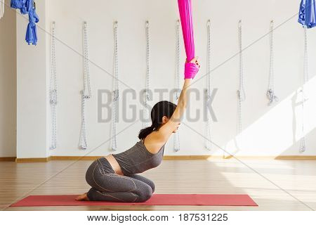 Woman stretches back holding hands on hammock. Aerial antigravity cobra yoga pose, woman does exercises, meditate in calm position trying to achieve peaceful state of mind and body