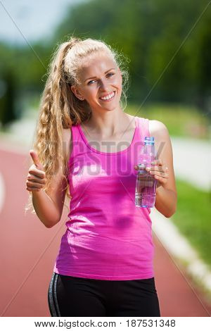 Young woman is drinking water after jogging on sunny day.