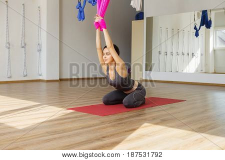 Young woman with closed eyes stretches back holding hands on hammock front view. Aerial antigravity cobra yoga pose, woman does exercises, meditate in calm position