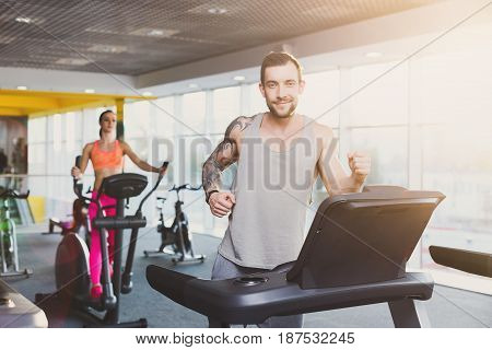 Ypoung man running on treadmill in fitness club. Cardio workout. Healthy lifestyle, guy and woman training in gym. Flare effect