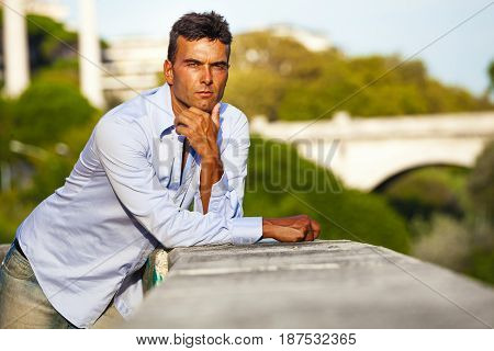 Handsome and charming serious Italian man outdoors leaning on a wall. Rome, Italy. Bridge on the River Tiber in the background. Trees and green. Serious expression.