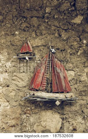 HERAKLION GREECE - JULY 16 2016: Sale of traditional local souvenirs in the historic center of the city. Wooden sailboat. Stylization. Toning.