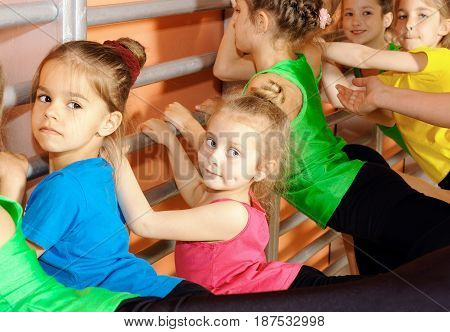 Happy little gymnasts doing exercise in gym