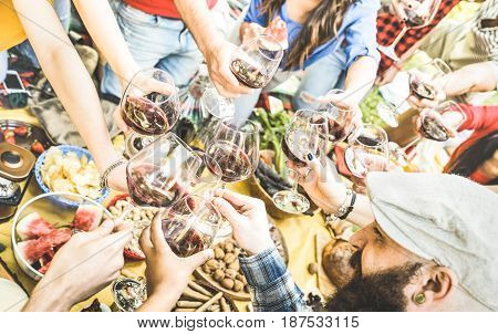 Top view of friend hands toasting red wine glass and having fun outdoor cheering at picnic winetasting - Young people enjoying summer time together at lunch bbq garden party - Youth friendship concept