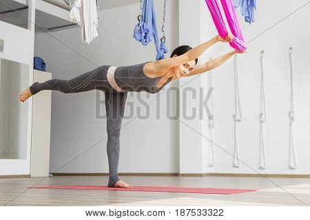 Adult woman practices balancing stick anti-gravity yoga position in studio. Girl stretches with help of hammock in gym, aerial yoga concept