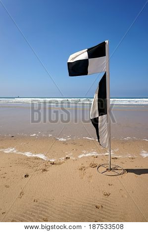 Flag On A Deserted Beach Indicating Safe Swimming And Surfing Zones